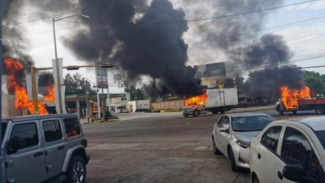 Vehículos incendiados durante una enfrentamiento de grupos armados con fuerzas federales en Culiacán tras la captura del hijo del Chapo.