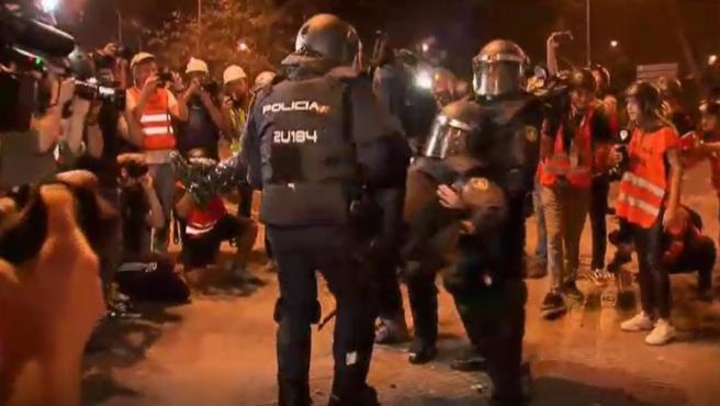 Agentes antidisturbios trasladan a un compañero herido durante los incidentes en la Via Laietana de Barcelona.