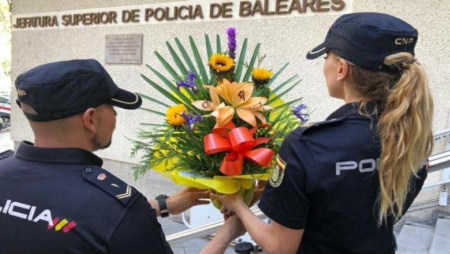 Dos agentes sostienen el ramo de flores depositado en la Jefatura Superior de Policía de Baleares.