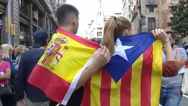 Una pareja, él con la bandera de España y ella con una estelada, se abrazan en Barcelona.