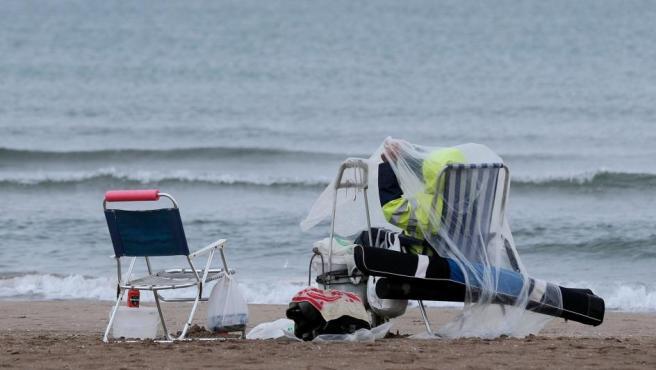 Una persona se protege de la lluvia con un plástico en la playa de la Malvarrosa.
