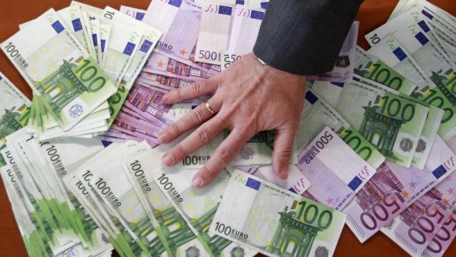 Una mano sobre una pila de dinero, en una imagen de archivo.