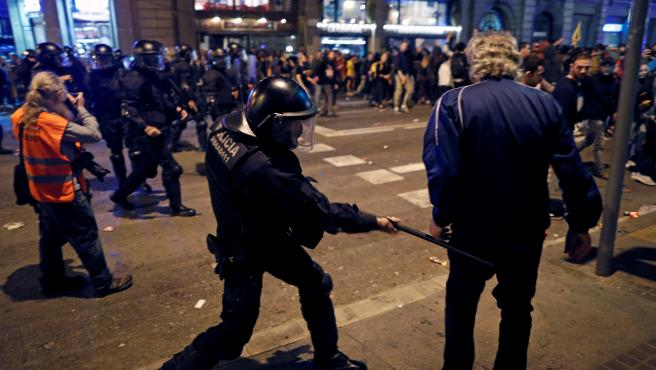 Un mosso carga contra un manifestante en Via Laietana.