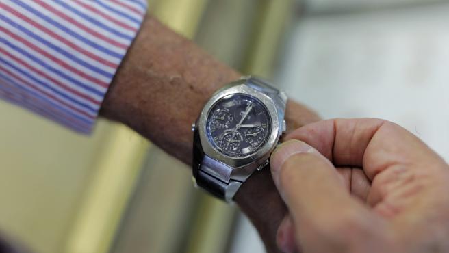 Un hombre mueve la manecilla del reloj para cambiar la hora, en Madrid, a 23 de octubre de 2019.
