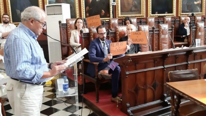 Los regidores de Cort en el Ayuntamiento muestran carteles reivindicativos en el pleno.