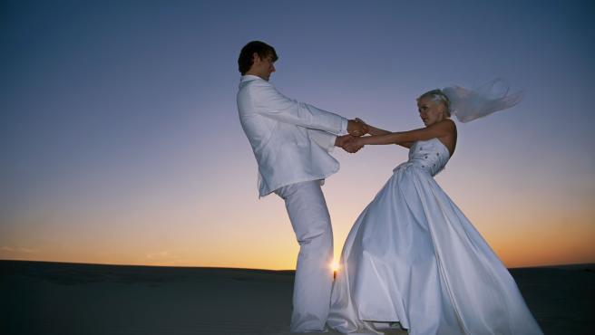 Una pareja de novios en la playa, al amanecer, en una imagen de archivo.