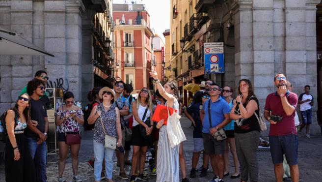 Varios turistas se fotografían en una de las calles cercanas a la Plaza Mayor de Madrid.