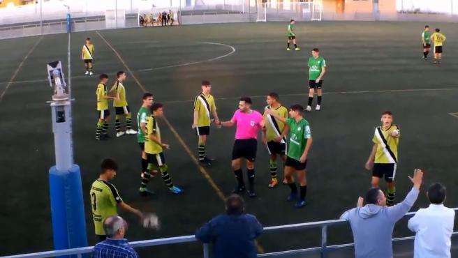 Un árbitro detiene un conato de bronca entre jugadores y aficionados.