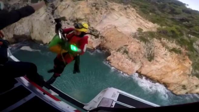 Un rescatador desciende del helicóptero frente a la Cueva del Llop Marí, en Jávea