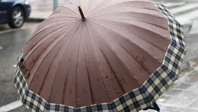 Una mujer pasea bajo su paraguas por Madrid.