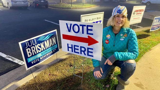 Julie Briskman posa junto a propaganda electoral.
