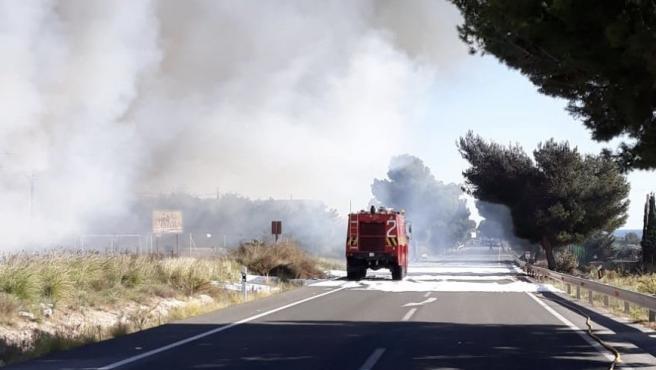 Un camión de bomberos junto al vertedero incendiado cerca del aeropuerto.