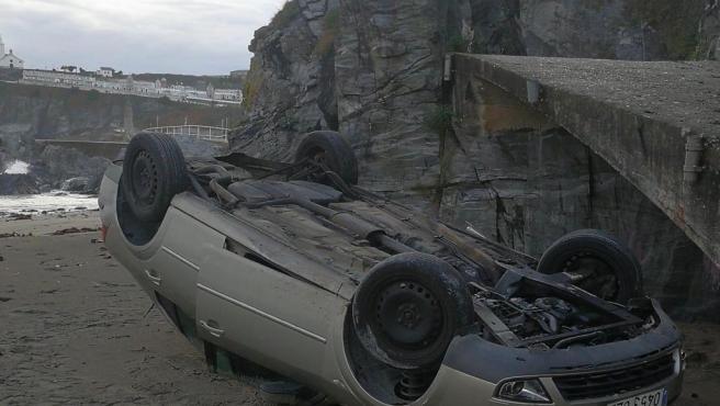 Vehículo volcado en la Playa Tercera de Luarca.