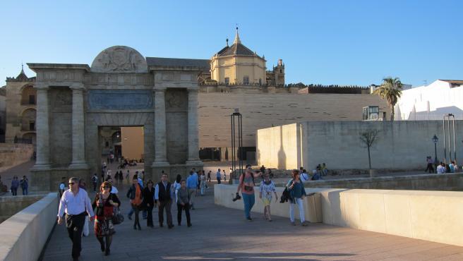 Turistas pasean por el Puente Romano