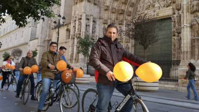 El candidato de Cs al Senado por Sevilla Ángel Mayo y el portavoz de Cs en el Ayuntamiento de Sevilla, Álvaro Pimentel, realizan un paseo en bicicleta junto a la catedral con otros miembros del partido