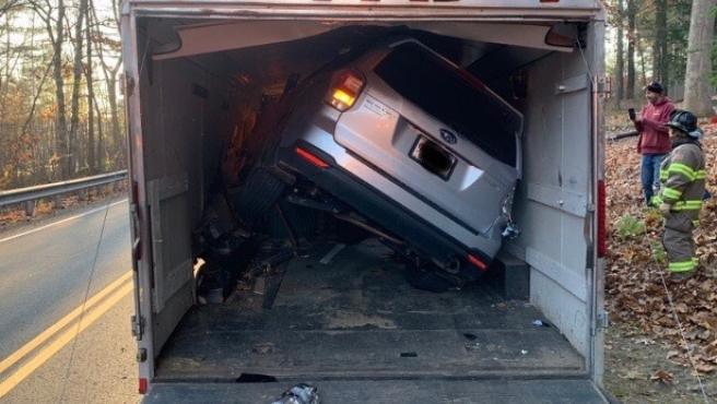 El Subaru de la mujer se quedó atascado en el remolque de un camión.