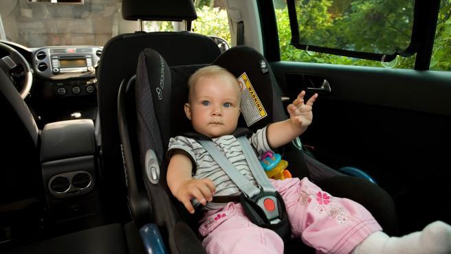 Imagen de un bebé en una silla adaptada en el interior de un vehículo.