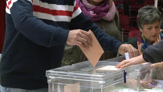 Un elector deposita su voto al Senado en una urna