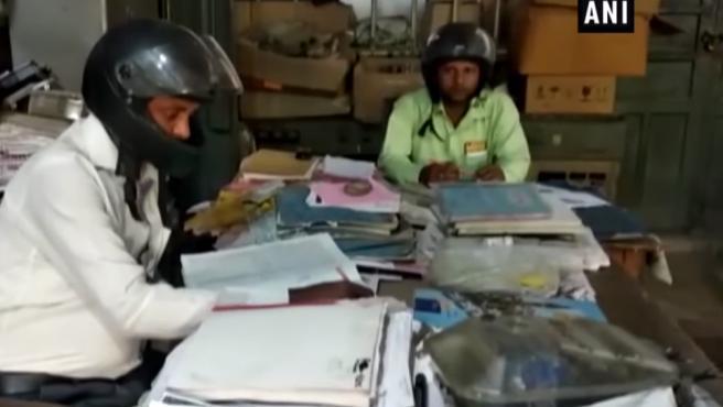 Funcionarios indios trabajan con casco de moto para evitar lesiones por caídas de objetos de su edificio.