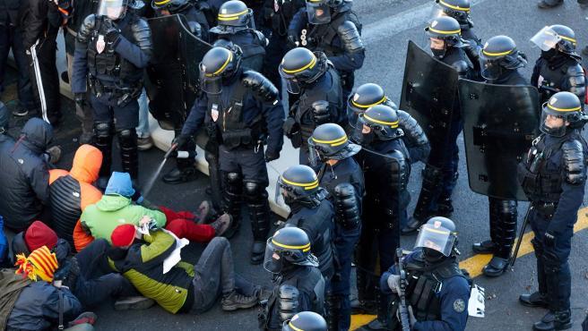 Antidisturbios franceses desalojan a manifestantes en la frontera entre España y Francia.