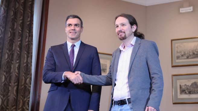 El presidente del Gobierno en funciones, Pedro Sánchez y el líder de Podemos, Pablo Iglesias, se estrechan la mano en el Congreso de los Diputados tras firmar el principio de acuerdo para compartir un gobierno de coalición tras las elecciones generales.