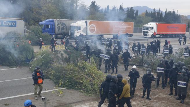 Los Mossos desalojan a los manifestantes que cortaban la AP-7 con barricadas de troncos, en Salt (Girona).