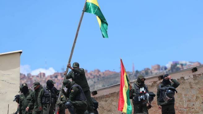 Policías de La Paz izan una bandera de Bolivia.
