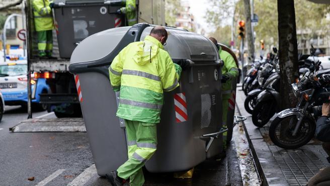 Operarios municipales reponen contenedores de basuras en Barcelona