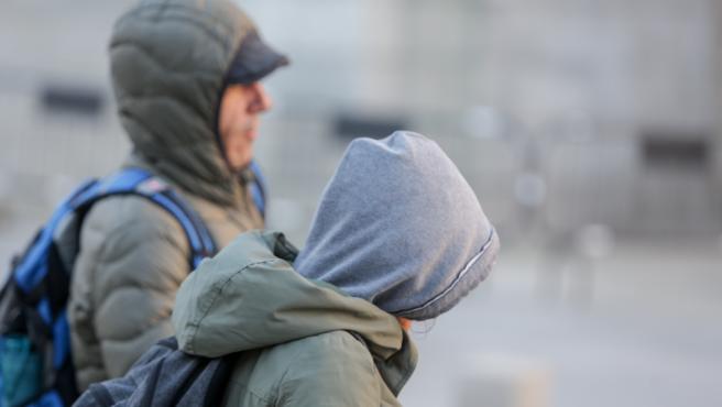 Dos jovenes se protegen del frío con abrigos y gorros mientras pasean durante un día de viento por Madrid (España), a 8 de noviembre de 2019.