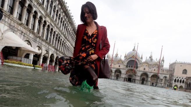 Una turista pasea por una inundada plaza de San Marcos, en Venecia (Italia).