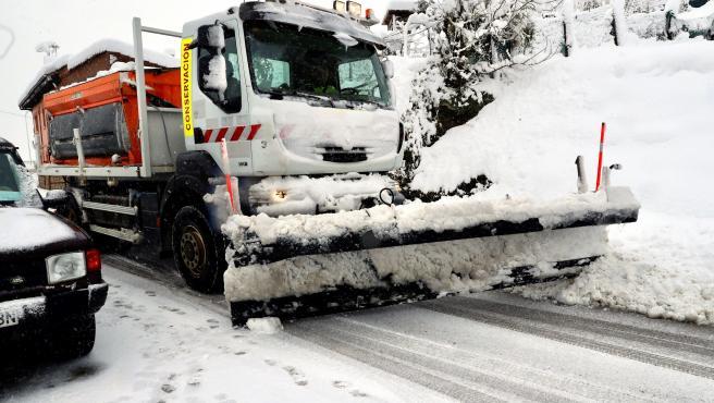 Una máquina quitanieves despeja una carretera cubierta de nieve.