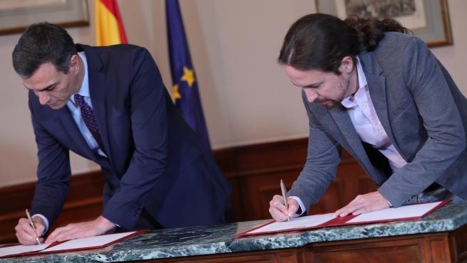 Pedro Sánchez y Pablo Iglesias durante la firma de su acuerdo para un Gobierno de coalición.