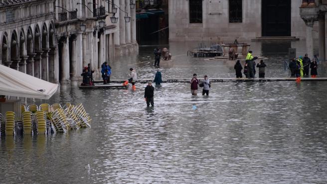 Varias personas caminan por la inundada plaza de San Marcos.