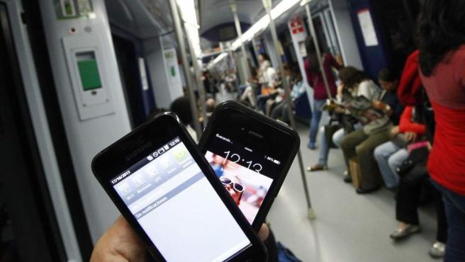 Imagen de archivo de personas mirando sus teléfonos móviles en el metro.