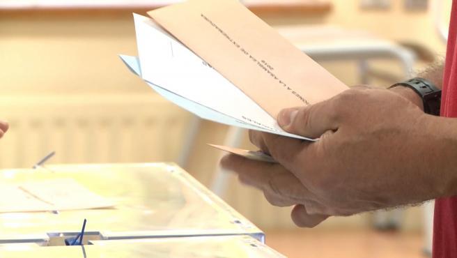 Un elector con las papeletas del 26M junto a una urna.