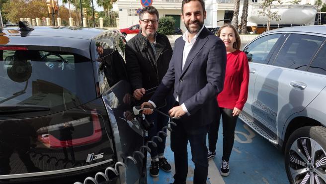 Daniel Pérez recarga un coche eléctrico junto con los ediles socialistas Jorque Quero y Alicia Murillo