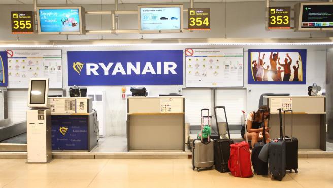 Pasajera, esperando en un mostrador de facturación de Ryanair.