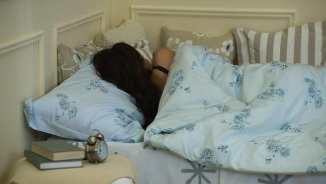 Una mujer duerme tapada con un edredón nórdico, en una imagen de archivo.
