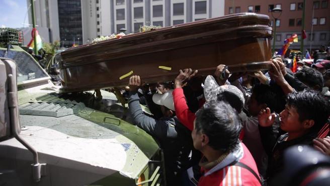 Manifestantes colocan un féretro sobre un vehículo militar en La Paz (Bolivia), durante una gran marcha de protesta desde El Alto hasta la capital.