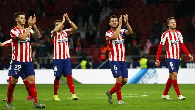 los jugadores del Atlético saludan a la afición al acabar un partido de Liga.