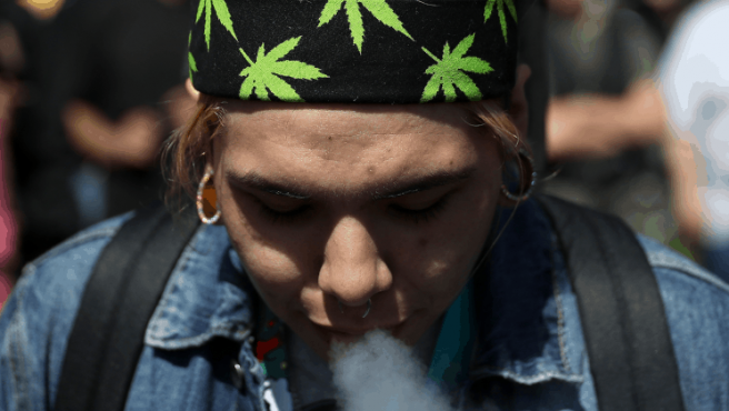 Una persona fumando marihuana.
