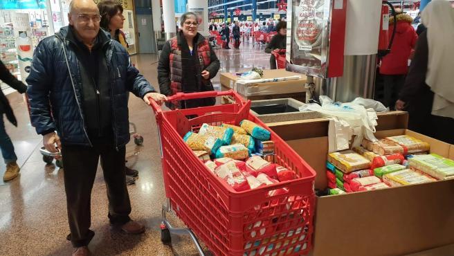 Una persona dona un carro lleno de productos en el marco de la Gran Recogida de alimentos