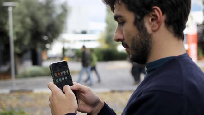 Un joven compra con su teléfono móvil.