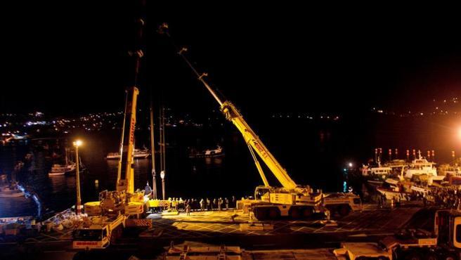Dos grúas tratan de izar el narcosubmarino cargado con droga que se hundió cuando había sido remolcado al puerto de Aldán (Pontevedra), tras ser hallado en la costa gallega abandonado por sus tripulantes.