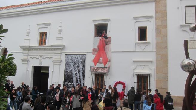 Alumnos de un instituto de Mérida despliegan un lazo rojo en la Asamblea.