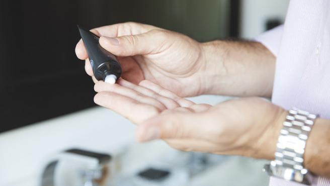 Un hombre se aplica una crema de manos, en una imagen de archivo.