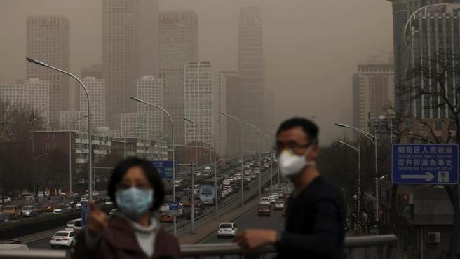 Un hombre y una mujer se protegen con máscaras de una nube de contaminación que cubre la ciudad de Pekín (China).