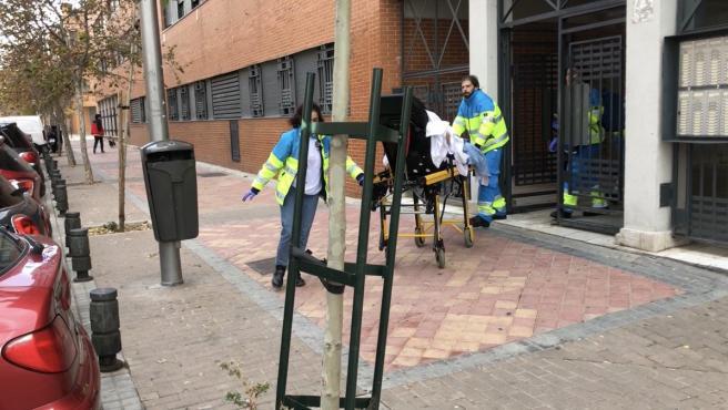 Joven apuñalada en su domicilio del madrileño barrio de Vallecas es transportada en camilla hacia la ambulancia por trabajadores de emergencias.