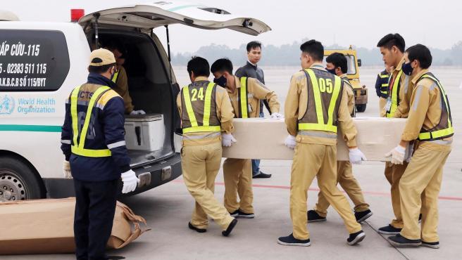 Trabajadores aeroportuarios trasladan los féretros con los cuerpos sin vida hallados en el interior de un camión refrigerador en Reino Unido, en el Aeropuerto Internacional de Noi Bai, en Hanoi, Vietnam