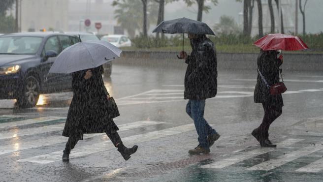 Imagen de archivo de varias personas bajo la lluvia.
